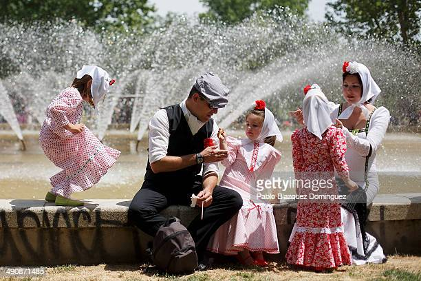 A family dressed as 'chulapos' have some food during the San Isidro festivities at Pradera de San Isidro park on May 15 2014 in Madrid Spain During...