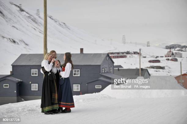 A family dressed in bunad which is traditional Norwegian dress look at pictures of a religious confirmation ceremony they are attending in...