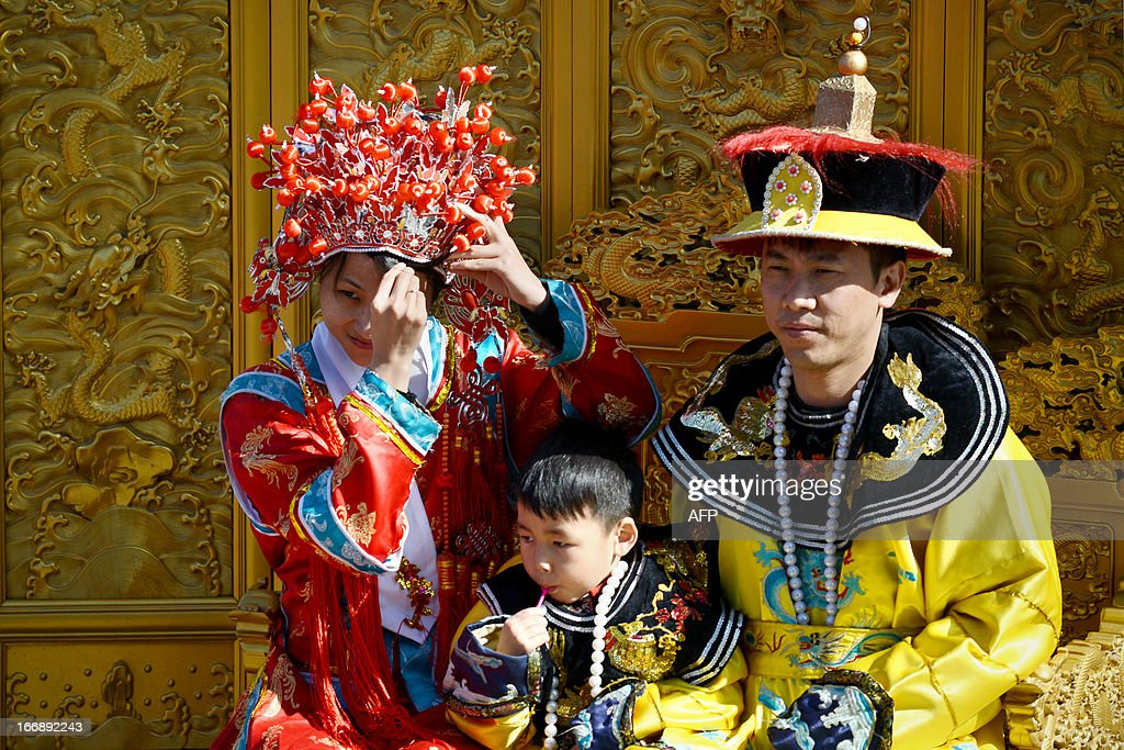 A family dressed in Qing Dynasty clothing prepares to take a photo at a park in Beijing on April 18, 2013. The historic 700 year old park includes a 45 metre man-made hill which was built to provide a favourable Feng Shui environment for the nearby Forbidden City.