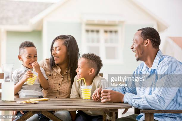 Family drinking juice in backyard