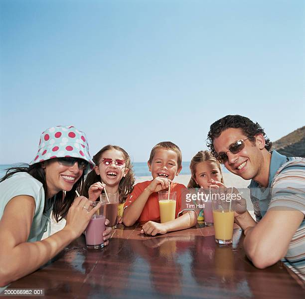 Family drinking milkshakes at table outdoors, portrait