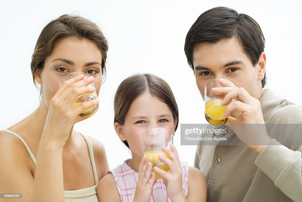 Family drinking orange juice, all looking at camera
