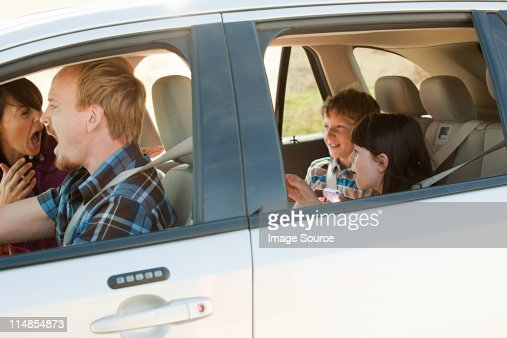 Family driving in car, parents shouting at children