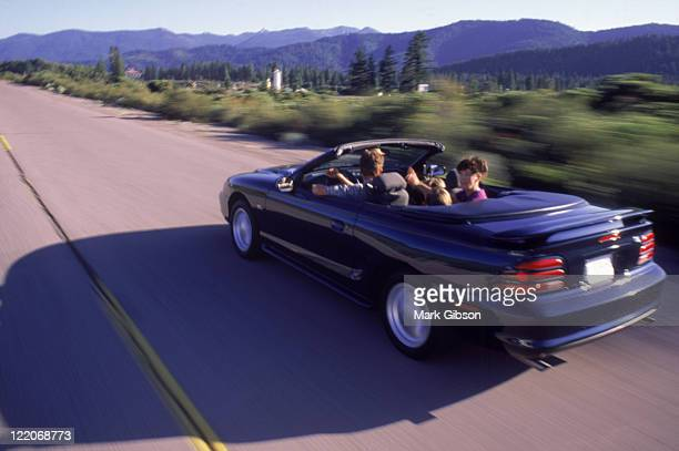 Family driving in convertible Ford Mustang