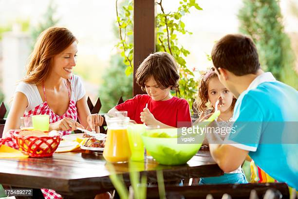 Family Eating Barbecue Outdoors.