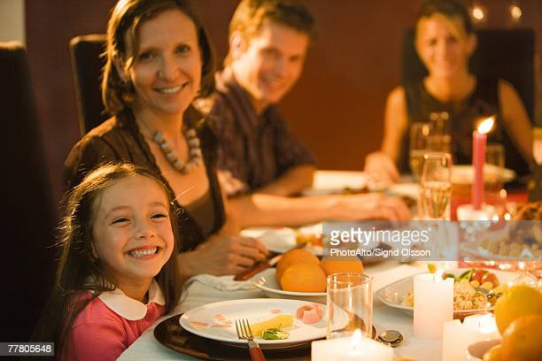 Family eating festive dinner, looking toward camera, smiling