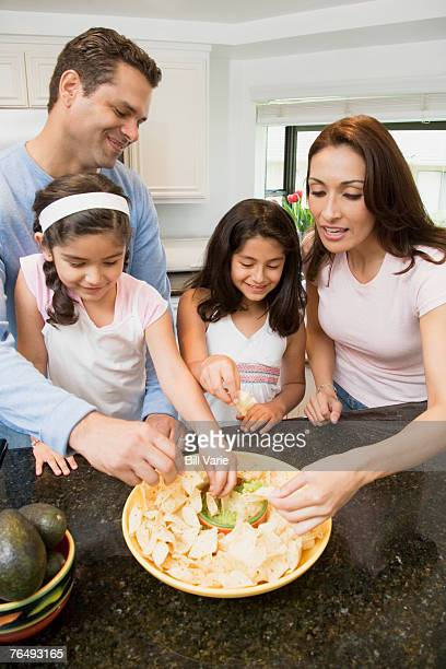 Family eating guacamole and chips