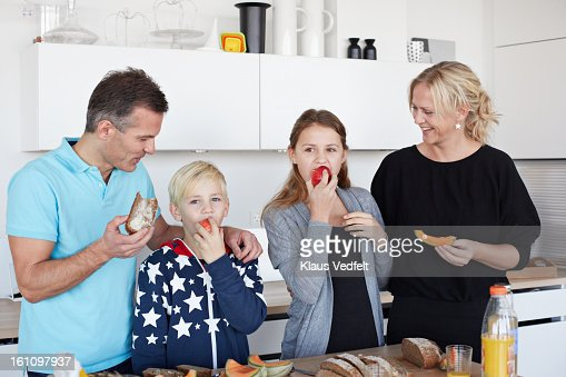 Family eating healthy breakfast in kitchen : Stock Photo