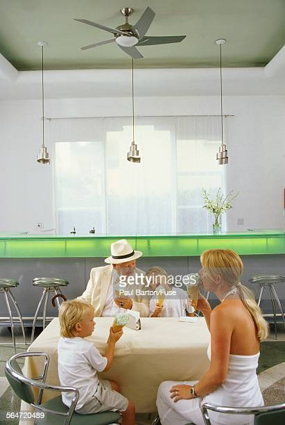 Family Eating Ice Cream in Cafe with Grandpa