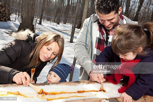 Family eating maple taffy on sticks