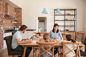 Family Eating Meal In Open Plan Kitchen Together