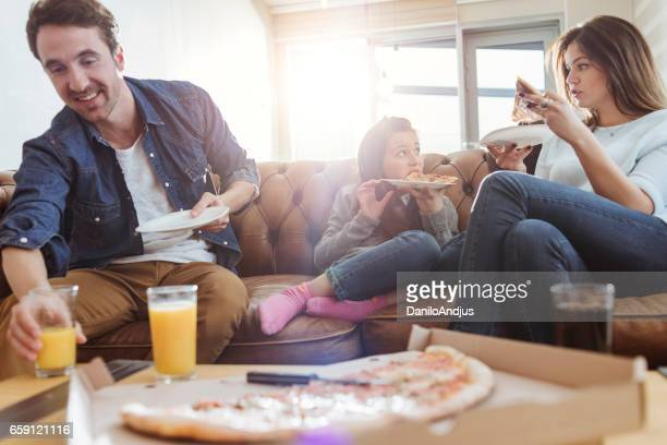 family eating pizza in the living room