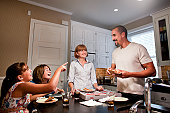 Family eating pizza together laughing