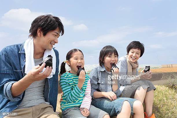 Family eating rice ball on field