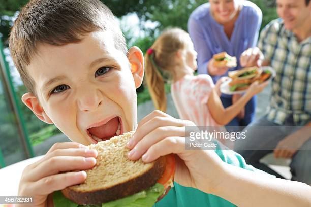 Family eating sandwiches, boy close to camera