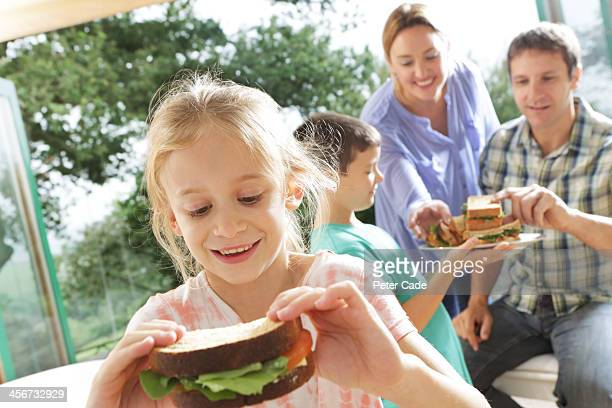 Family eating sandwiches, girl close to camera