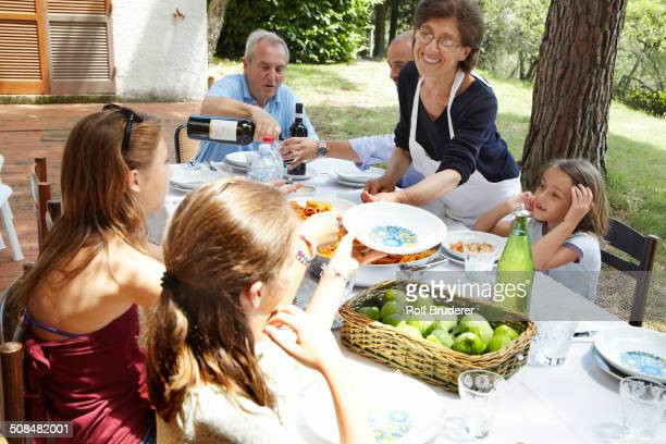 Family eating together at table outdoors