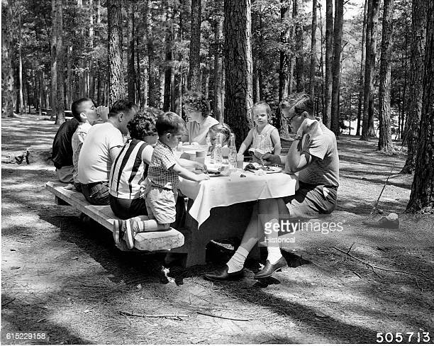 A family eats a picnic lunch at the Brushy Lake Recreation Area in the W B Bankhead National Forest Alabama 1963 | Location Brushy Lake Recreation...