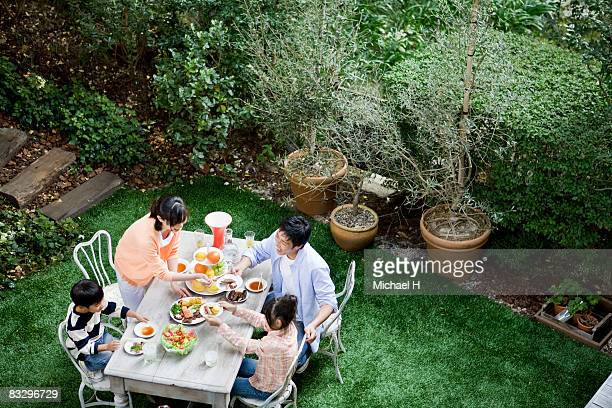 Family eats in garden,pleasures of a happy home