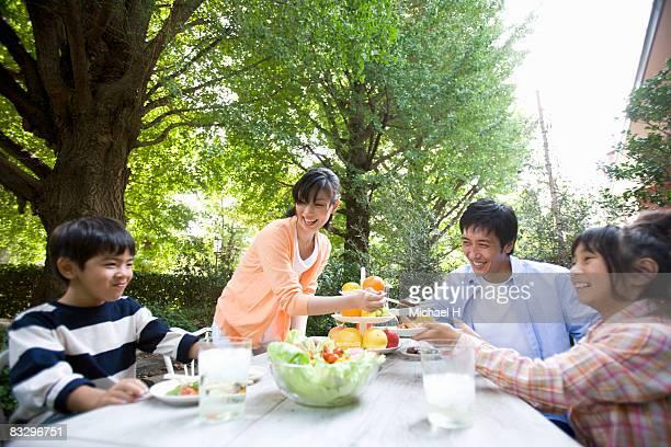 Family eats in garden,pleasures of a happy home