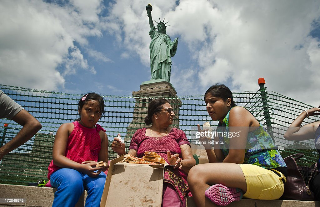 A family eats pizza in front of the Statue of Liberty on the first day it is open to the public after Hurricane Sandy on July 4, 2013 on the Liberty Island in New York City. The statue was mostly spared by the storm, but the surrounding infrastructure was badly damaged.