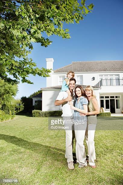Eine Familie umarmen vor einem großen Hause