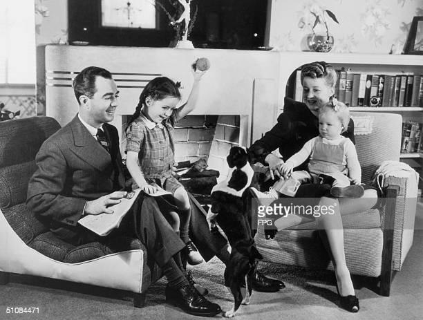 A family enjoy quality time together at home circa 1935