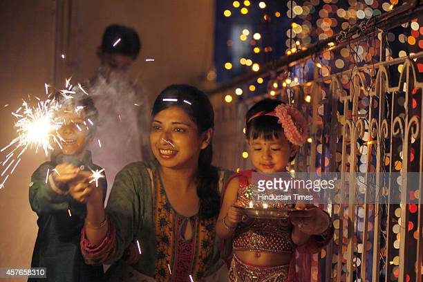A family enjoy sparklers on the eve of Hindu festival Diwali on October 22 2014 in New Delhi India Diwali also known as Deepavali and the festival of...
