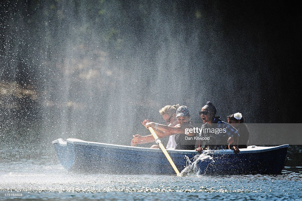 A family enjoy the spray from a fountain on the boating lake in Victoria Park on August 1 2013 in London England A heatwave has returned to much of...