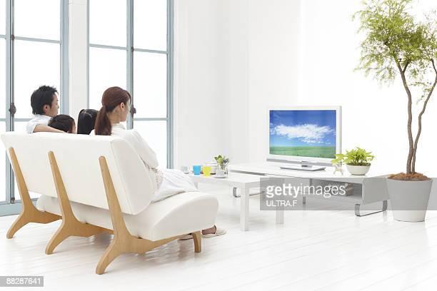 A family enjoy watching TV.