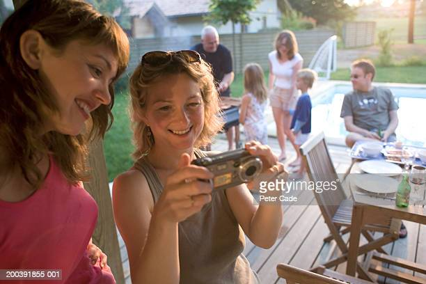 Family enjoying a barbeque, two woman in foreground using a camcorder