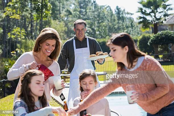 Familia comiendo hamburguesas cookout con patio