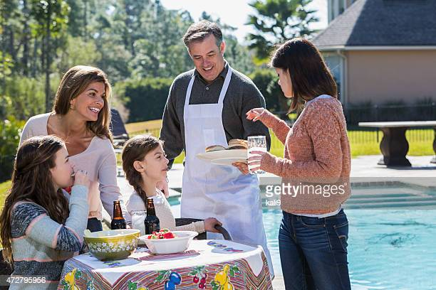 Family enjoying backyard cookout eating hamburgers