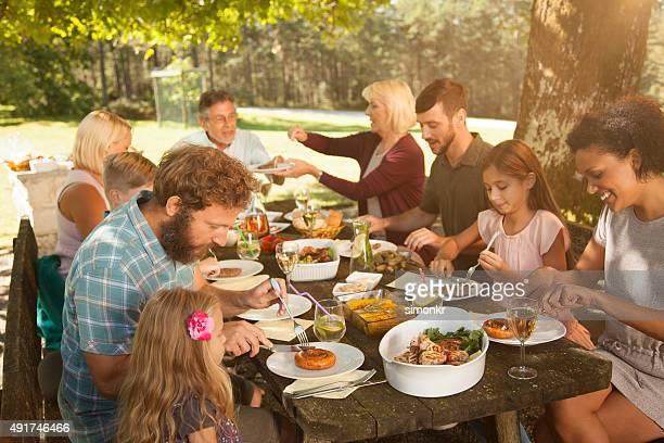 Famille appréciant un barbecue à l'extérieur