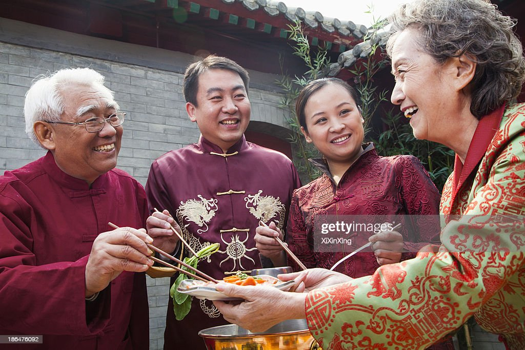 Family enjoying Chinese meal in traditional Chinese clothing : Stock Photo