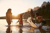 Family Enjoying Evening Swim In Countryside Lake