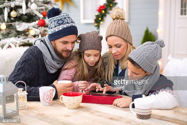 Family enjoying in hot drinks outdoors in front of house.