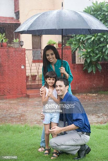 Family enjoying in rain in a park