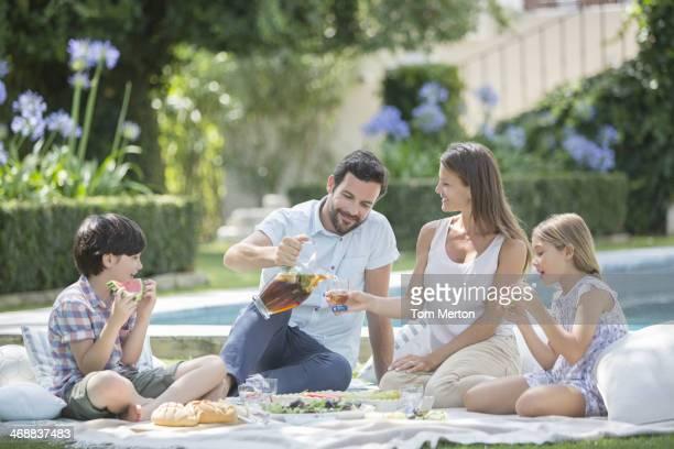 Family enjoying picnic at poolside