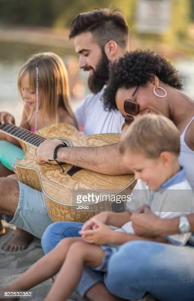 Famille appréciant les sons de la guitare sur la plage.