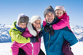 Happy family with two children on winter vacation in mountain. Young father and cheerful mother giving piggyback ride little daughter and smiling son. Portrait of happy family looking at camera with s