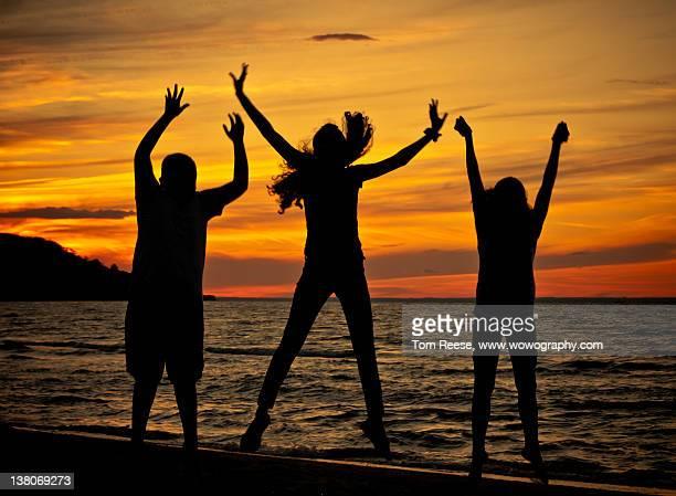 Family enjoys on beach in sunset
