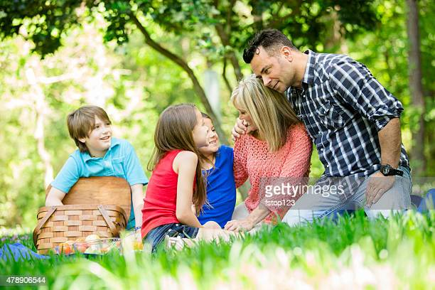 Family enjoys picnic outdoors in summer season. Park or yard.