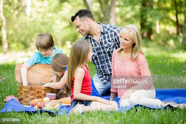 Family enjoys picnic outdoors in summer season. Park or yard.