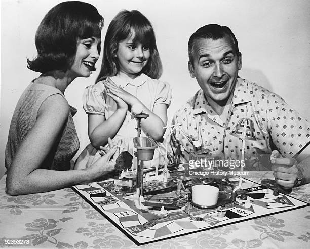 A family enjoys the board game 'Mouse Trap' ca1965