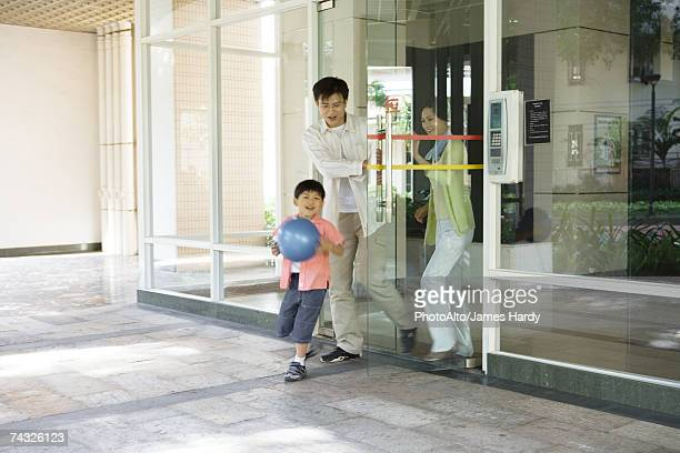 Family exiting apartment building lobby, boy carrying ball