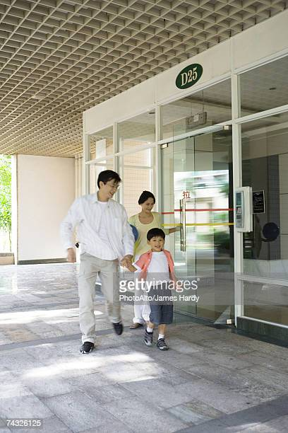 Family exiting apartment building lobby