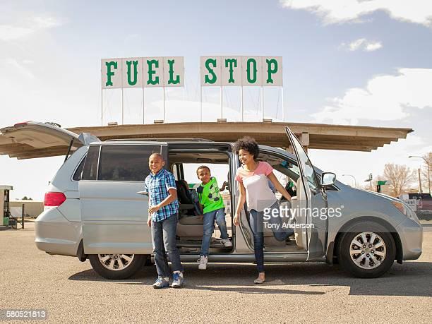 Family exiting minivan at gas station