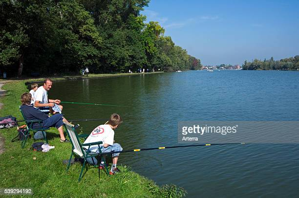 Family father and sons with fishing rods angling in lake Donkmeer East Flanders Belgium