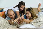 Family fighting over remote control, laughing